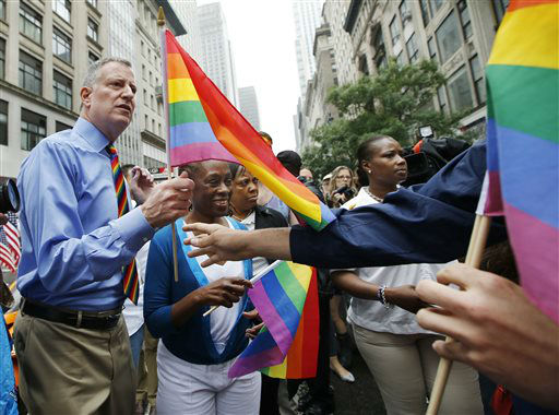 "<div class=""meta image-caption""><div class=""origin-logo origin-image none""><span>none</span></div><span class=""caption-text"">New York City Mayor Bill de Blasio, left, with his wife Chirlane McCray, second from left, accepts a rainbow-colored gay pride flag before the start of the Heritage Pride March.  (AP Photo/ Kathy Willens)</span></div>"