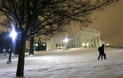 <div class='meta'><div class='origin-logo' data-origin='none'></div><span class='caption-text' data-credit='AP Photo/ Steve Helber'>A couple walks past the snow covered grounds of the State Capitol in Richmond, Va., Friday, Jan. 22, 2016.</span></div>