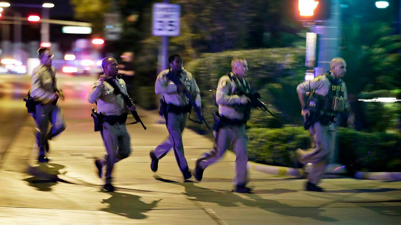 Police run to cover at the scene of a shooting near the Mandalay Bay resort and casino on the Las Vegas Strip, Sunday, Oct. 1, 2017, in Las Vegas.
