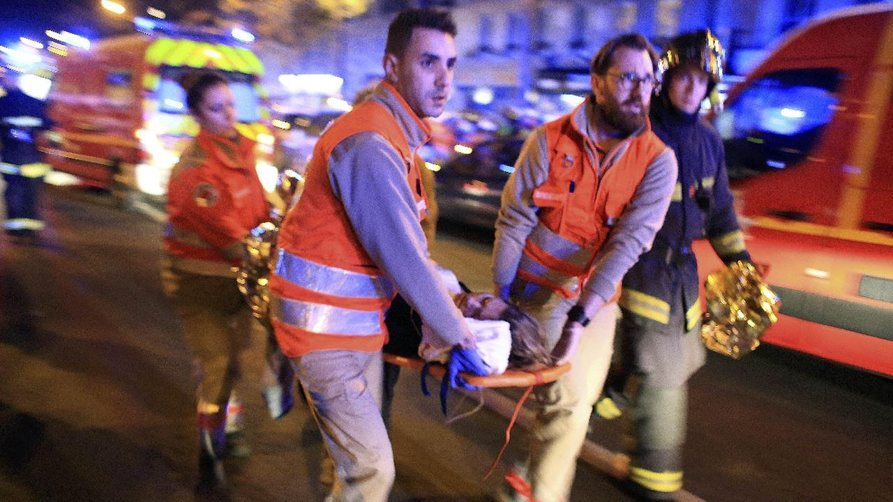 A woman is being evacuated from the Bataclan theater after a shooting in Paris, Friday Nov. 13, 2015. French President Francois Hollande declared a state of emergency and announced