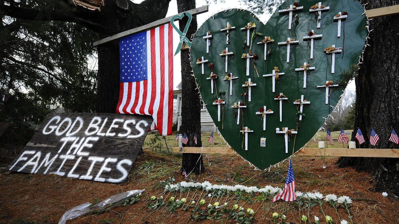 A memorial is displayed in a yard near the Sandy Hook Elementary School on the one-month anniversary of the mass shooting that left 26 dead, including 20 children in Newtown, Conn.