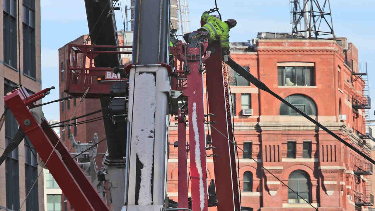 A worker fastens a cable to a portion of a collapsed crane, Saturday. Officials are working to determine why the crane that was being lowered during strong winds came crashing down