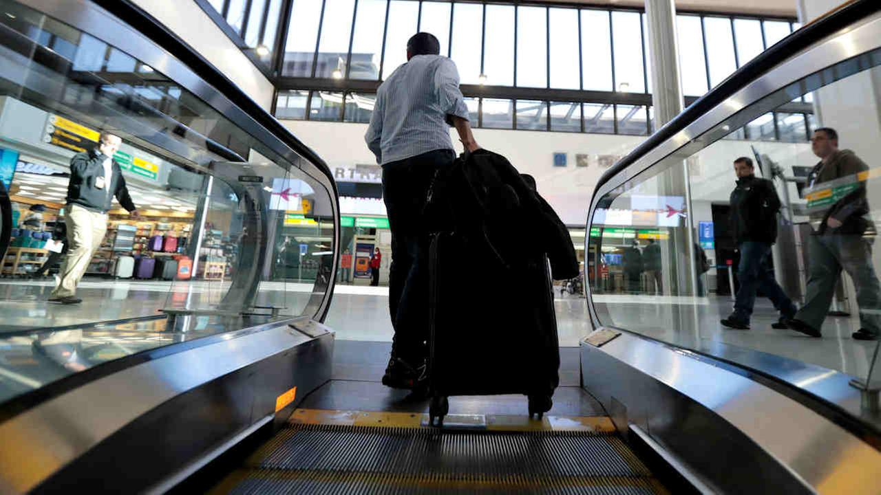 A traveler pulls luggage off an escalator at Newark Liberty International Airport, Tuesday in Newark, N.J.