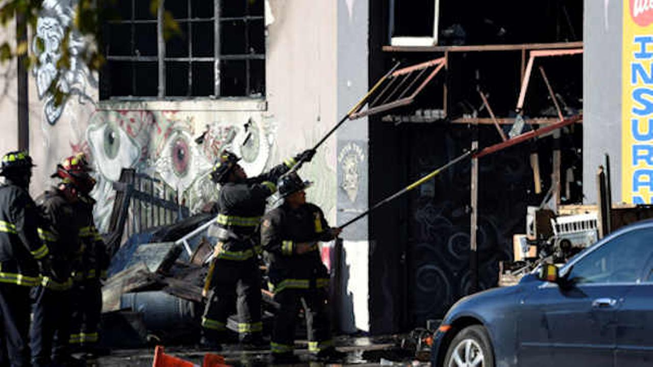 Firefighters clear an entry to a smoldering building after a fire tore through a warehouse party  (AP Photo/Josh Edelson)