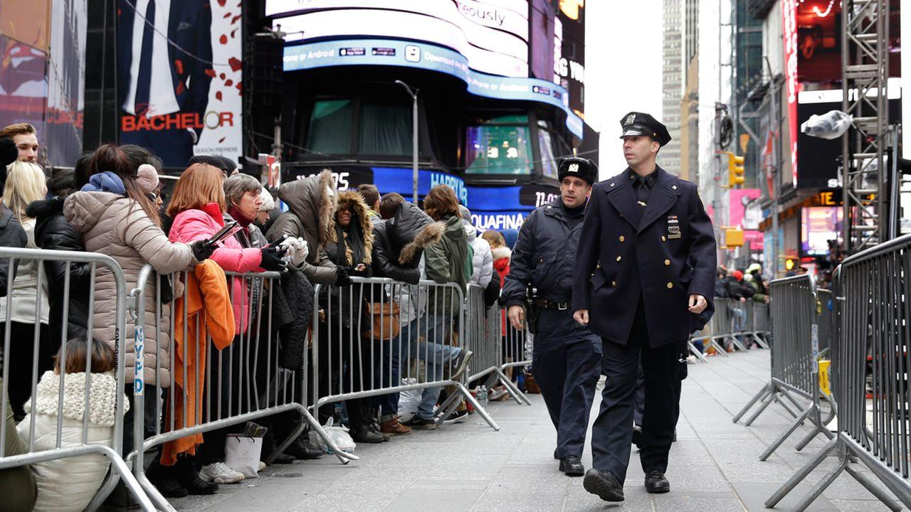 Police officers walk through the gathering crowds at Times Square in New York, Thursday, Dec. 31, 2015.