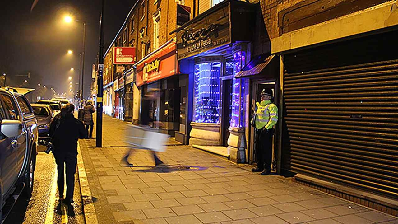A police officer stand outside an address in Birmingham, early Thursday March 23, 2017, where armed police have raided a flat overnight.