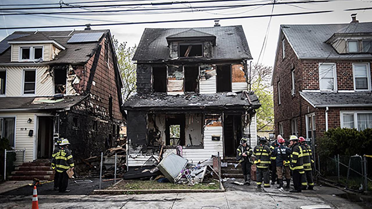 New York Fire Department personnel stand outside the scene of a deadly fire in Queens.  (Michael Appleton/Office of the Mayor via AP)