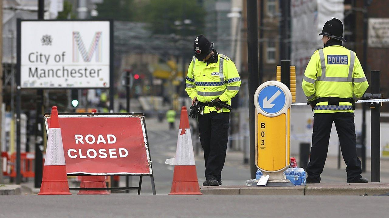 Police officers stand guard close to Victoria Railway Station in Manchester, Britain, Wednesday, after a suicide attack at an Ariana Grande concert.