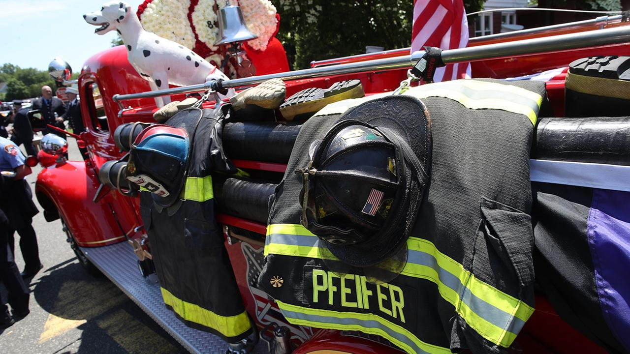 The jacket and helmet of retired New York City firefighter Raymond Pfeifer are hung from the side of a fire truck during his funeral service, Friday, June 2, 2017 in Hicksville