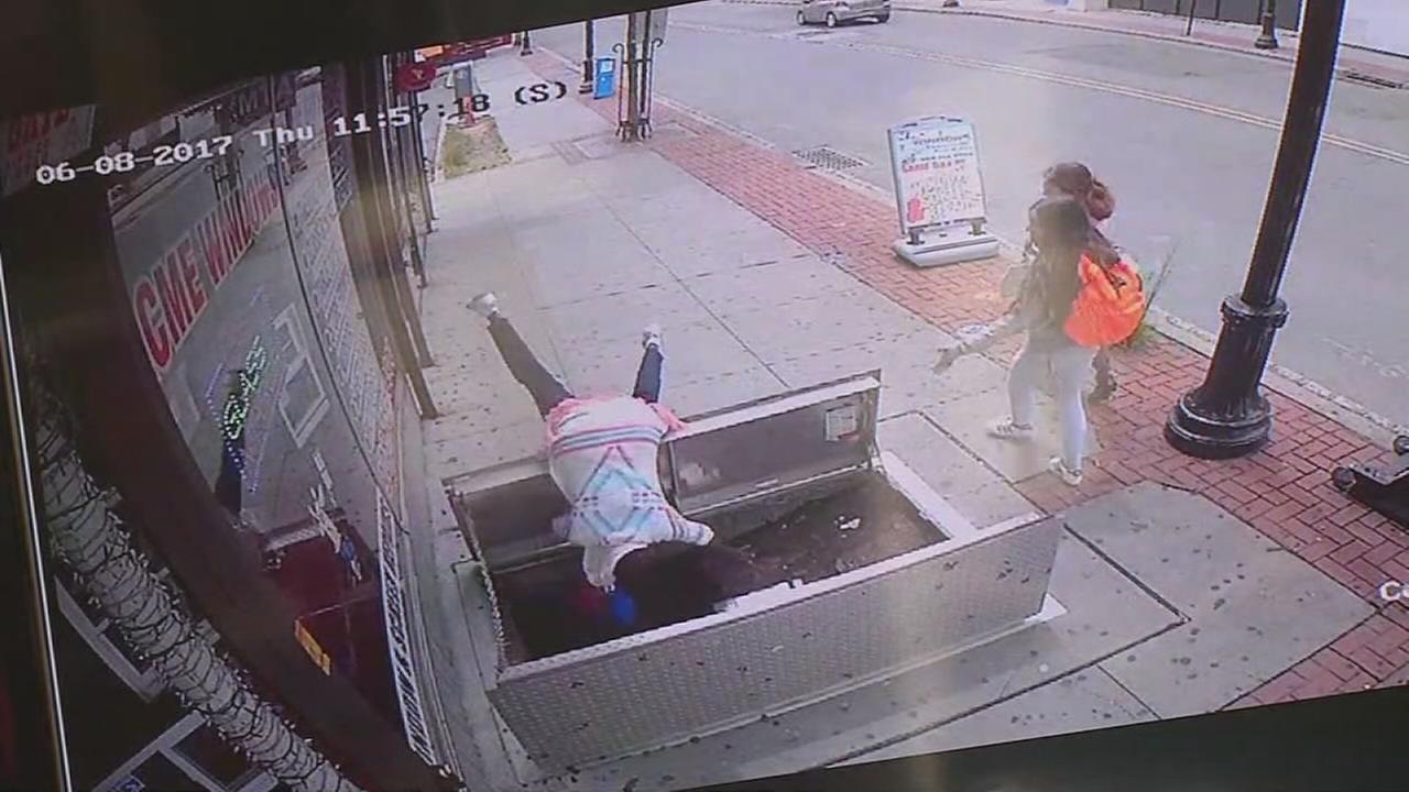 Raw: Video shows woman fall into sidewalk opening