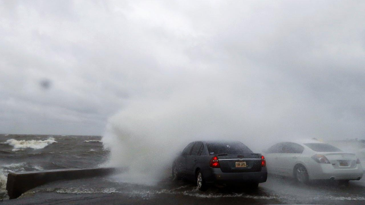 People sit in a car and watch the waves on the shore of Lake Pontchartrain as weather from Tropical Storm Cindy, in the Gulf of Mexico, impacts the region Tuesday.