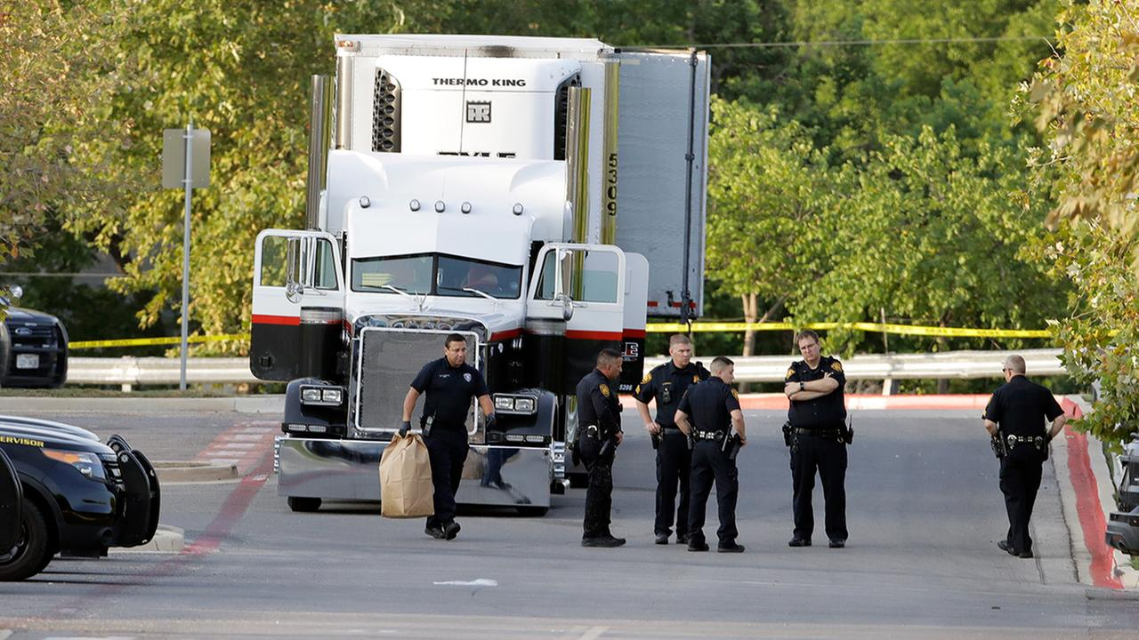 San Antonio police officers investigate the scene where eight people were found dead in a tractor-trailer. (AP Photo/Eric Gay)