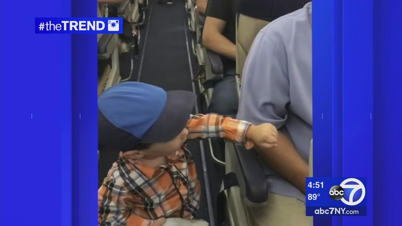 The Trend: Tiny passenger fist bumps others on a flight