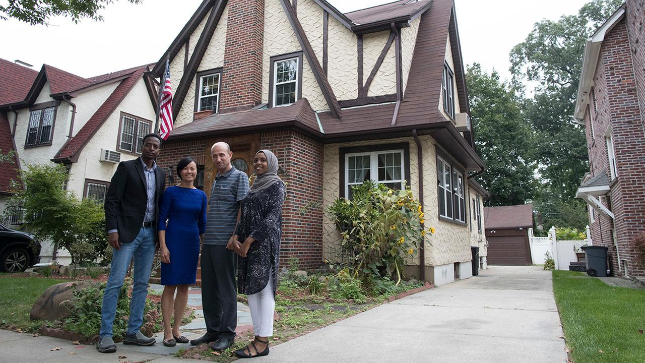 Abdi Iftin, of Somalia, Uyen Nguyen, of Vietnam, Eiman Ali, of Somalia, and Ghassan al-Chahada, of Syria pose for a photo outside President Donald Trumps boyhood home in Queens.