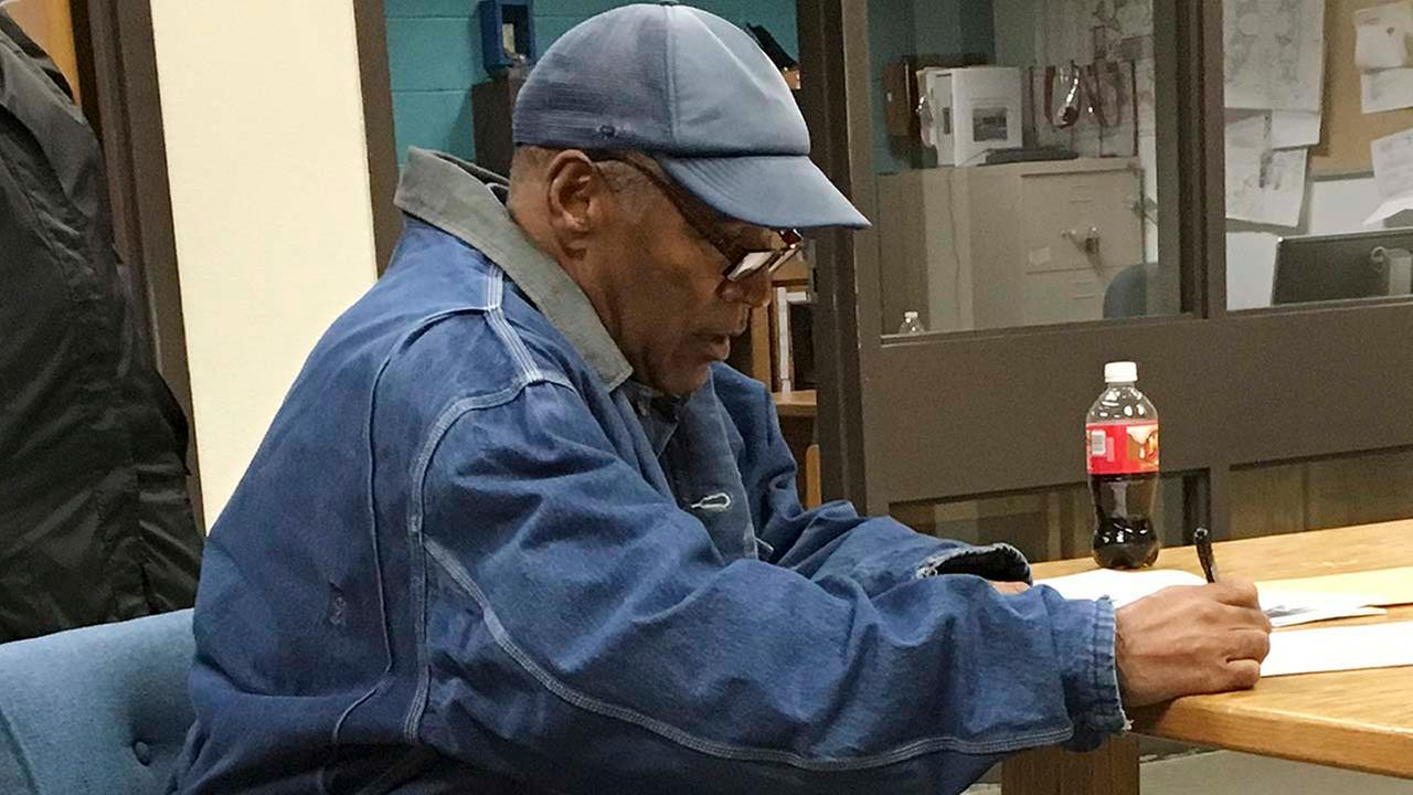 Former football legend O.J. Simpson signs documents at the Lovelock Correctional Center, Saturday, Sept. 30, 2017 (Brooke Keast/Nevada Department of Corrections via AP)