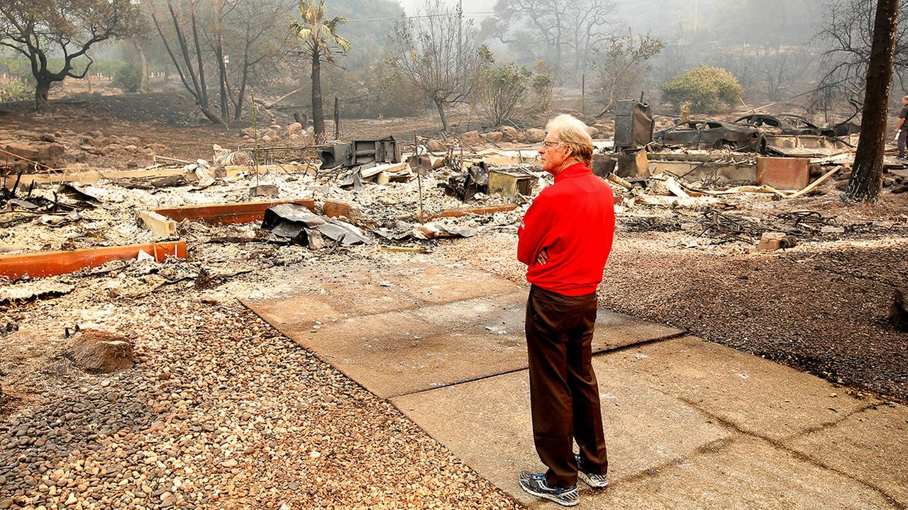 Mike Rippey looks over the charred remains of his parents home at the Silverado Resort. Charles Rippey, 100, and his wife Sara, 98, died when flames swept through the area Sunday