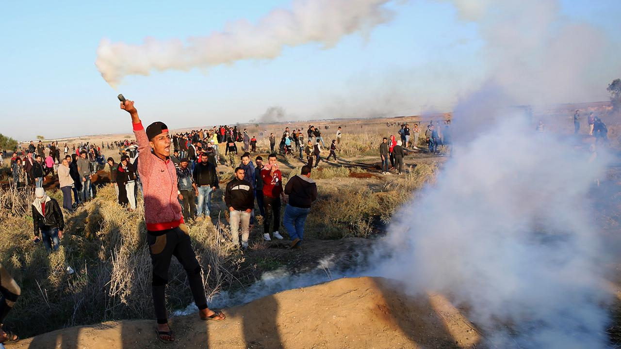 A Palestinian protester throws back a teargas canister that was fired by Israeli soldiers, during clashes on the Israeli border on Friday, Dec. 8, 2017.
