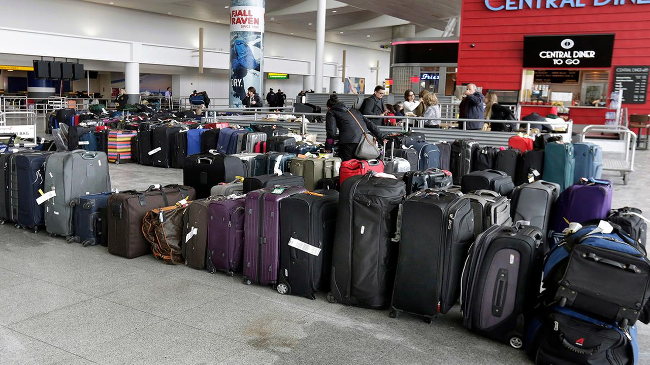 A woman looks through unclaimed baggage at New Yorks John F. Kennedy Airport Terminal 4, Monday, Jan. 8, 2018.  (AP Photo/Richard Drew)