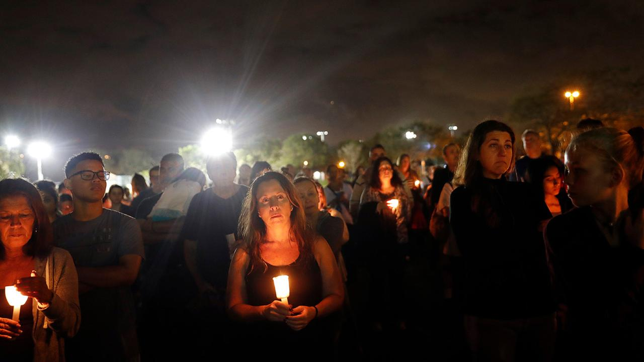 People participate in a candlelight vigil on Monday, Feb. 19, 2018, in memory the victims killed at Marjory Stoneman Douglas High School in Parkland, Florida.