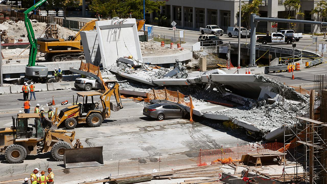 Crushed cars are shown under a section of a collapsed pedestrian bridge, Friday, March 16, 2018 near Florida International University in the Miami area.  (AP Photo/Wilfredo Lee)