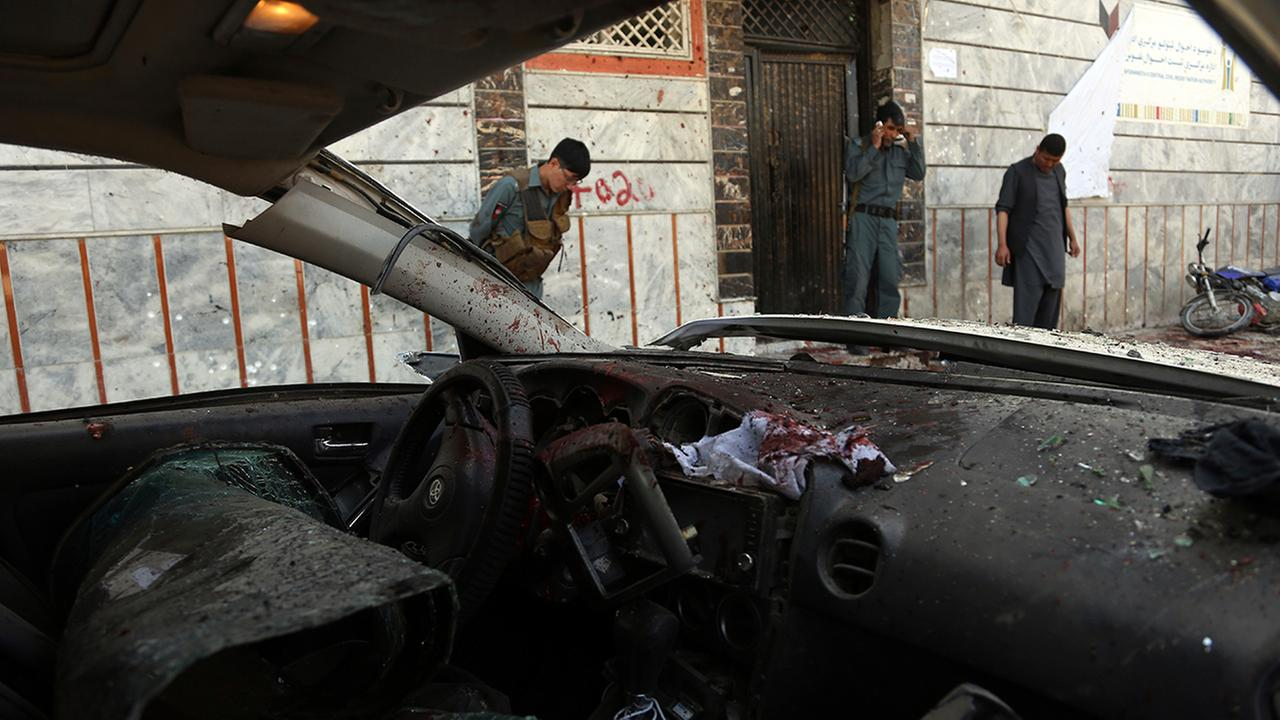 Afghan security personnel stand outside a voter registration center, after a suicide attack in Kabul, Afghanistan, Sunday, April 22, 2018. (AP Photo/Rahmat Gul)