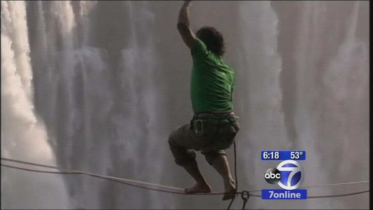 Two men walk across Victoria Falls on stretch of rope
