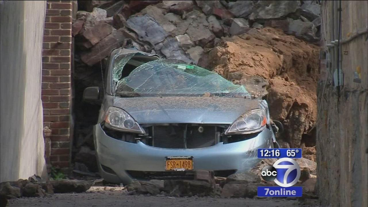 Three cars crushed under debris of wall collapse