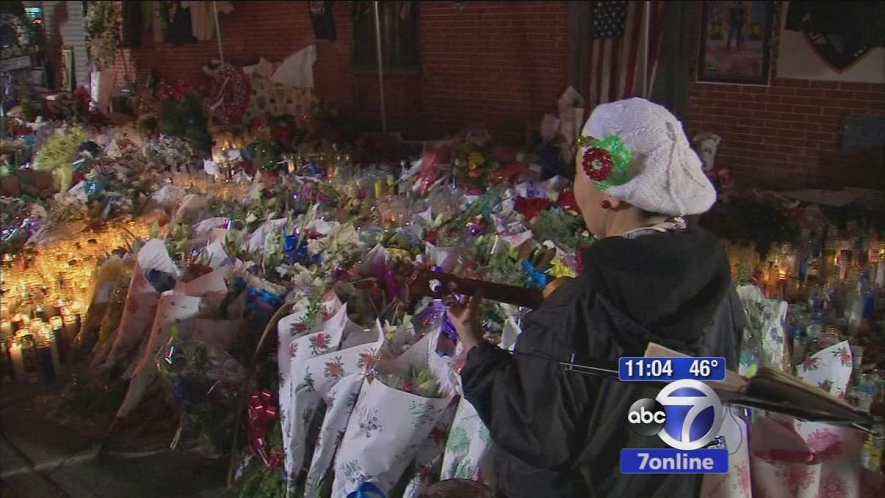Woman sings Christmas carols at shrine to fallen NYPD officers