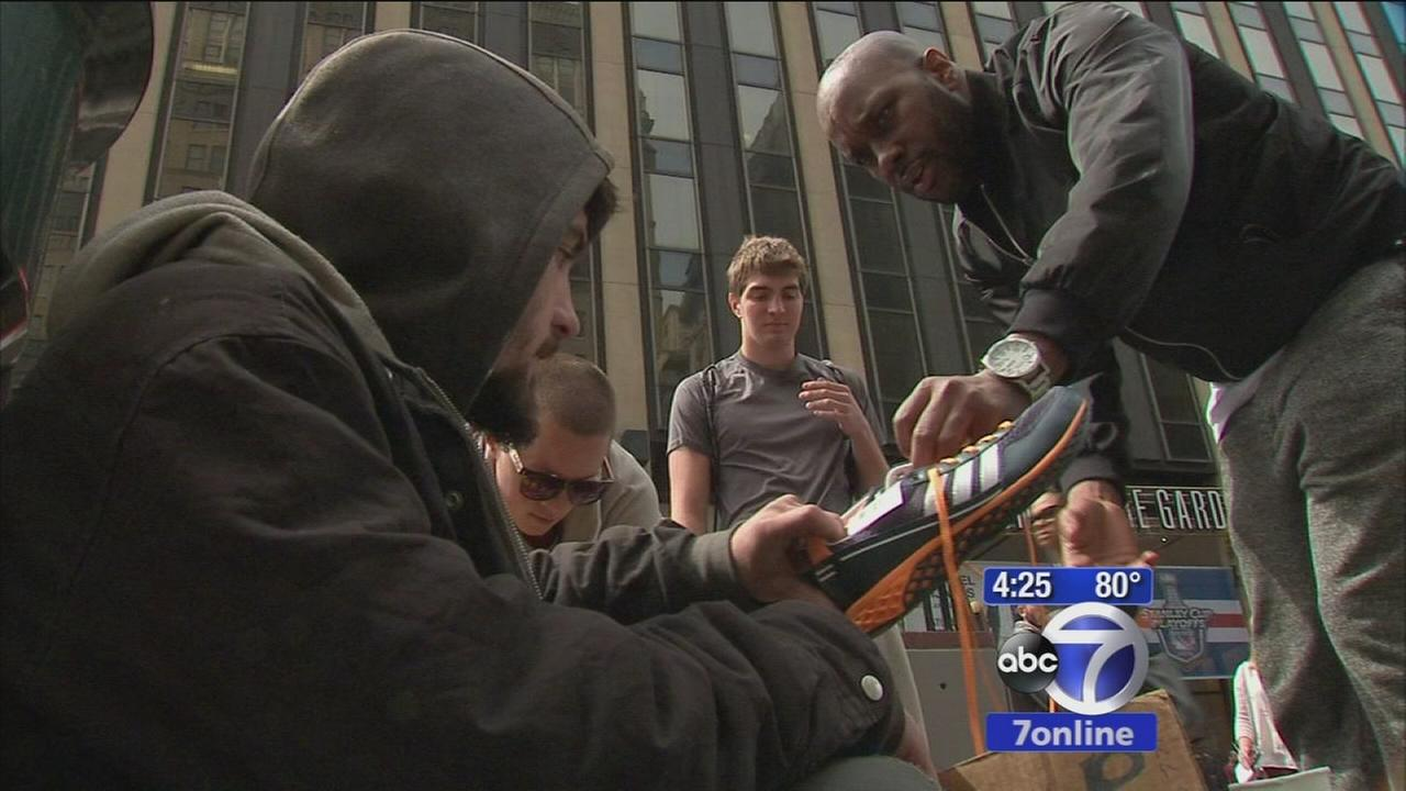 Good Samaritan giving sneakers to the homeless
