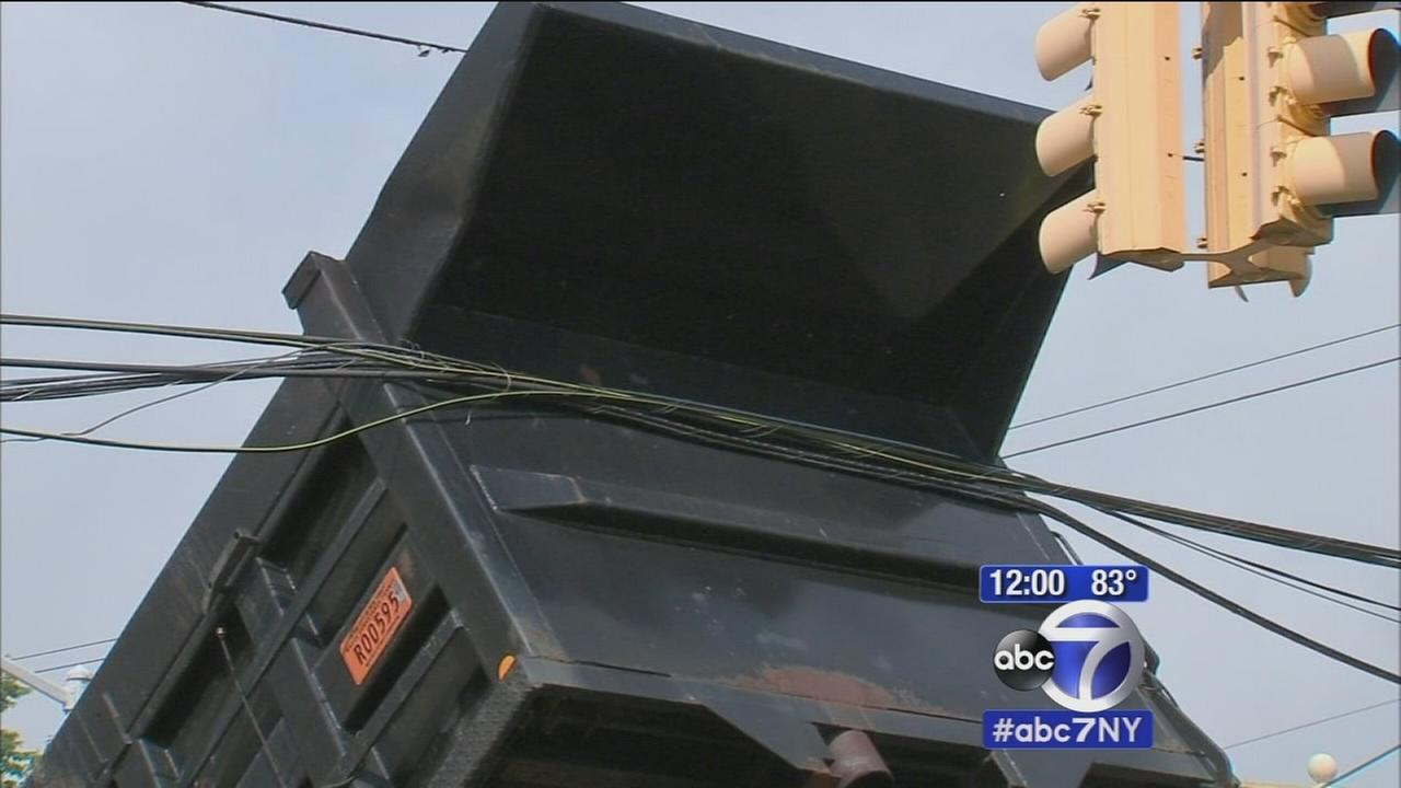 Dump truck downs power lines in Queens