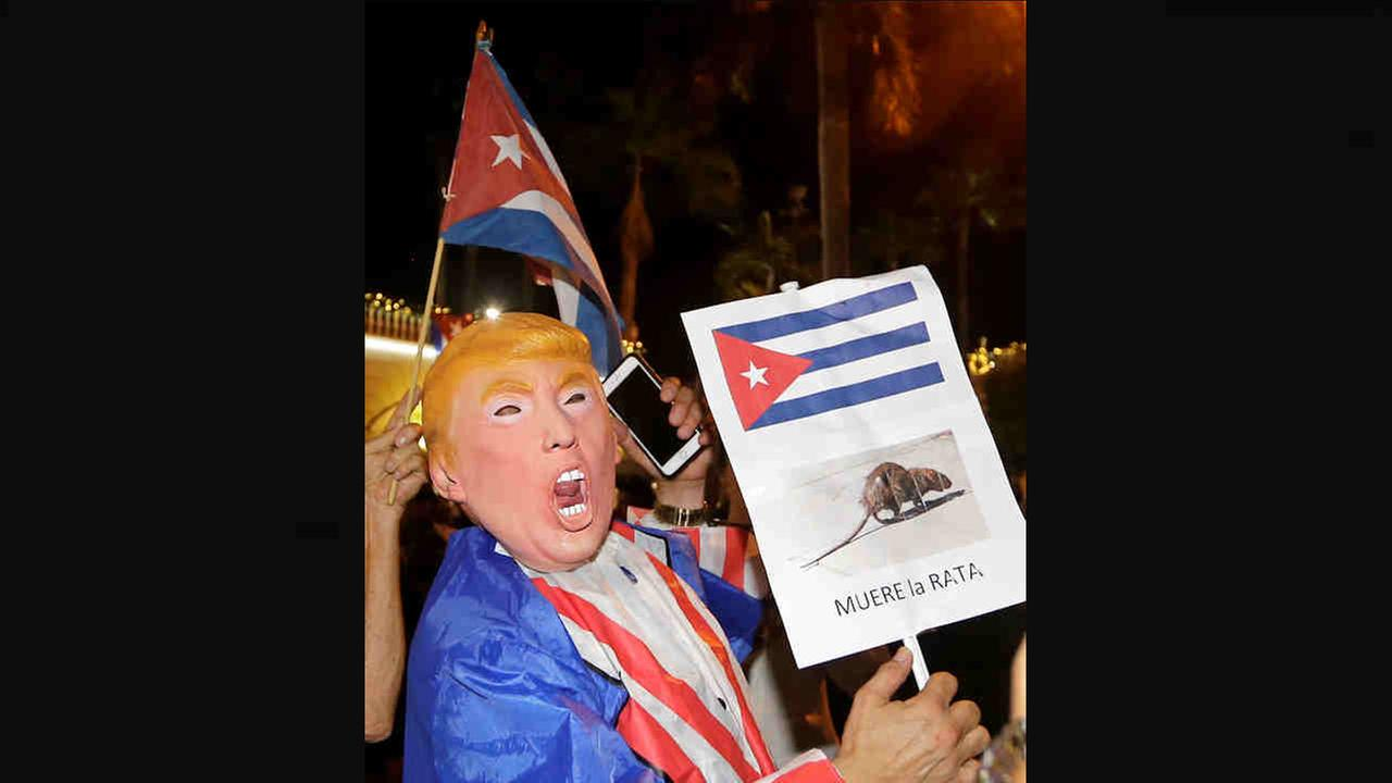 A person wearing a Donald Trump mask holds a sign in Spanish that reads the Rat Dies as he celebrates the death of Fidel Castro Saturday.Alan Diaz