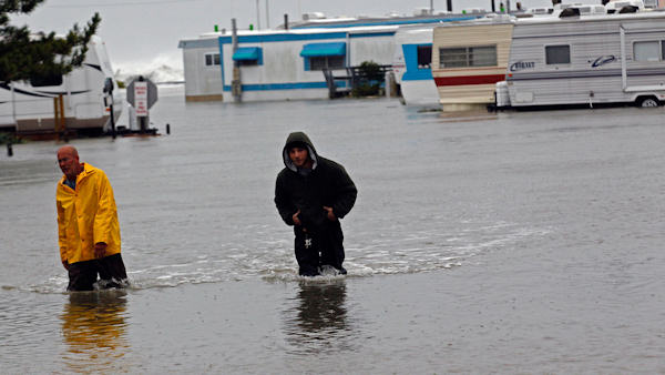 "<div class=""meta image-caption""><div class=""origin-logo origin-image none""><span>none</span></div><span class=""caption-text"">Terry Robinson, left, and Bobby Carnutte wade through floodwater caused by Hurricane Sandy at RV Park in Kitty Hawk, N.C., Oct. 29, 2012. Sandy flooding left many roads impassable. (AP/Gerry Broome)</span></div>"