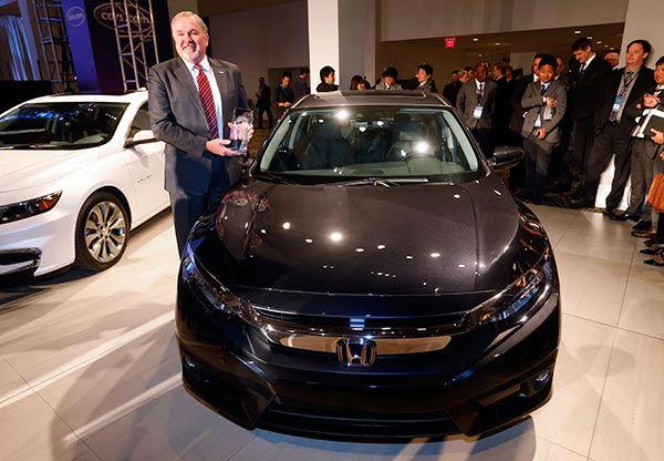 "<div class=""meta image-caption""><div class=""origin-logo origin-image none""><span>none</span></div><span class=""caption-text"">John W. Mendel, executive VP of American Honda Motor Co., Inc., poses with the Honda Civic, winner of the North American Car of the Year award.  (AP Photo/Paul Sancya)</span></div>"