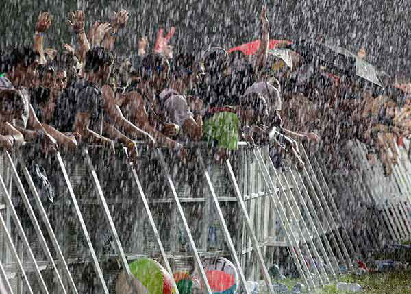 Fans wait in a downpour for Damian Marley and Nas to perform in 2011. <span class=meta>AP Photo/Nam Y. Huh</span>