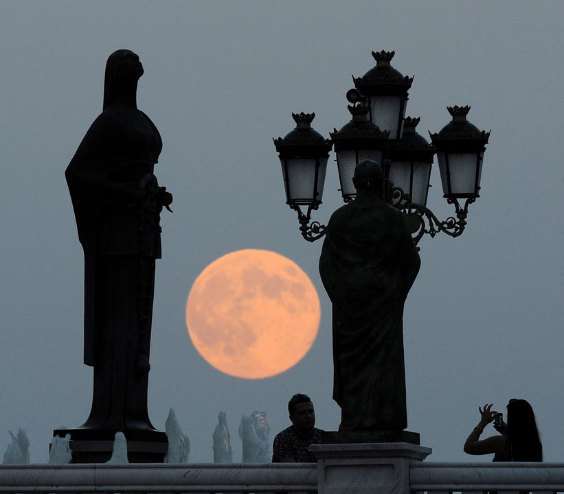"<div class=""meta image-caption""><div class=""origin-logo origin-image ""><span></span></div><span class=""caption-text"">People take photos as a perigee moon also known as a supermoon rises above in Skopje, Macedonia, Sunday, Aug. 10, 2014.  (AP Photo/Boris Grdanoski)</span></div>"