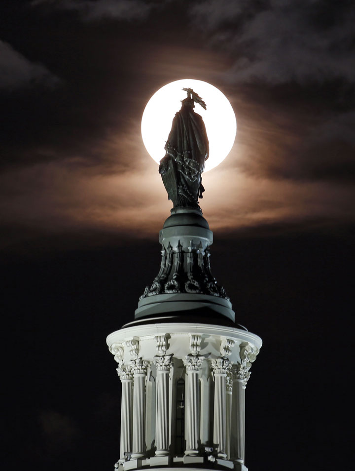"<div class=""meta image-caption""><div class=""origin-logo origin-image ""><span></span></div><span class=""caption-text"">The supermoon is seen as it rises through the clouds behind the bronze Statue of Freedom by Thomas Crawford atop the U.S. Capitol, Sunday, Aug. 10, 2014, in Washington.  (AP Photo/Alex Brandon)</span></div>"