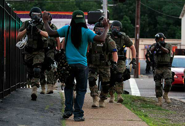<div class='meta'><div class='origin-logo' data-origin='none'></div><span class='caption-text' data-credit='AP Photo/Jeff Roberson'>Police wearing riot gear walk toward a man with his hands raised Monday, Aug. 11, 2014, in Ferguson, Mo.</span></div>