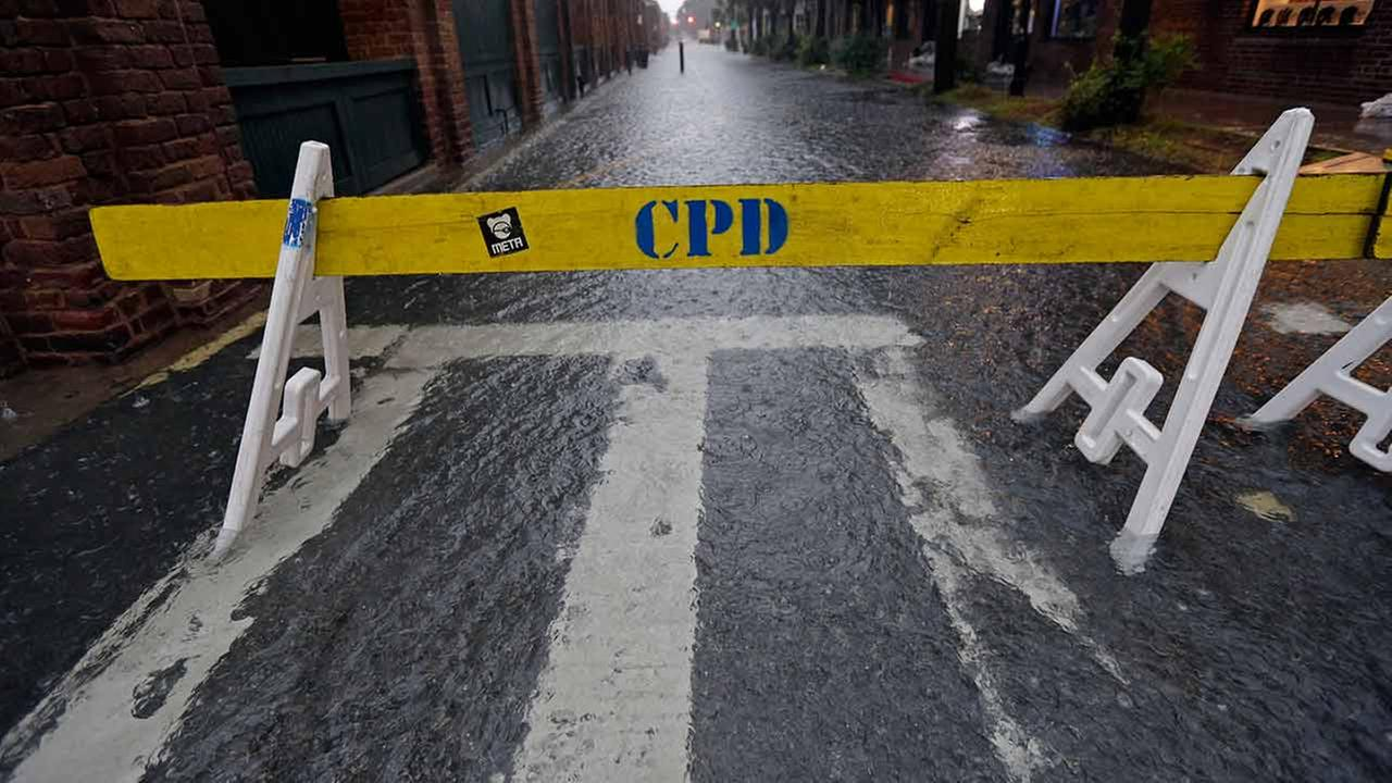A road block closes a flooded road along the City Market in downtown Charleston, S.C. on Oct. 3, 2015.
