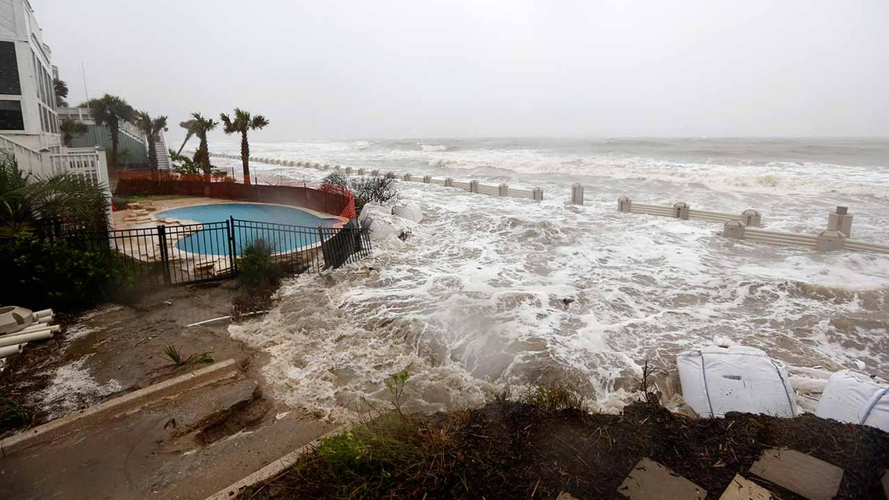 Waves crash over an experimental sea wall to protect homes during high tide on the Isle of Palms on Oct. 3, 2015.