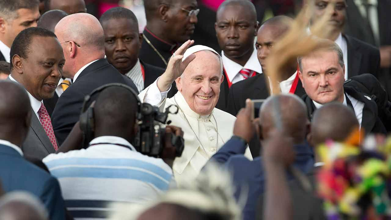 Pope Francis, center, waves to traditional dancers accompanied by Kenyas President Uhuru Kenyatta, left on his arrival at the airport in Nairobi, Kenya Wednesday, Nov. 25, 2015.