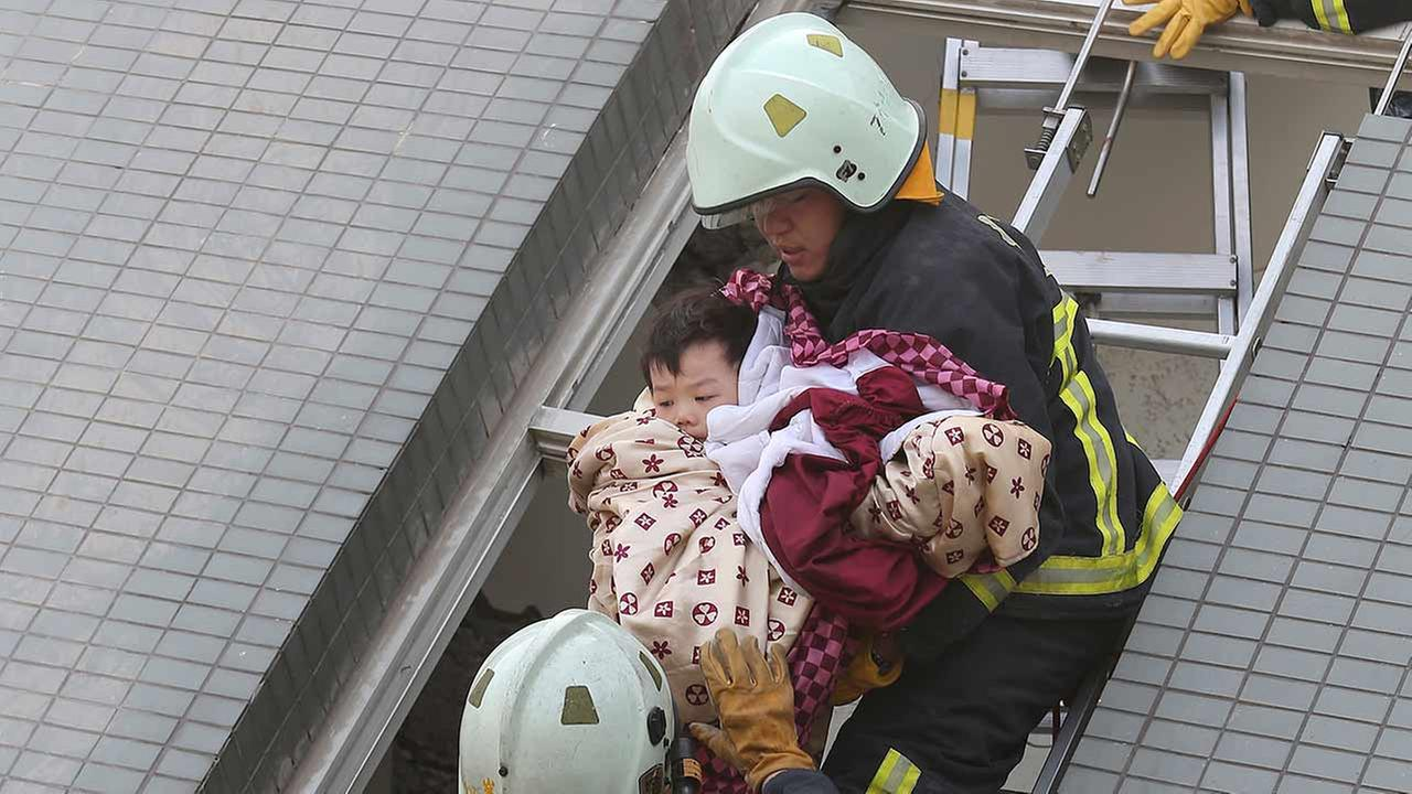 A child is rescued from a toppled building after a 6.4-magnitude earthquake in Tainan, Taiwan on Feb. 6, 2016. AP Photo