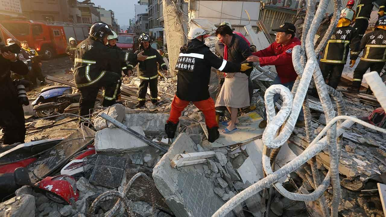 Rescue workers guide a man from the rubble of a toppled building after an earthquake in Tainan, Taiwan on Feb. 6, 2016.AP Photo