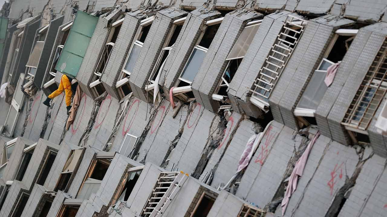 A rescue team member searches for missing people in a collapsed building, after an early morning earthquake in Tainan, Taiwan on Feb. 6, 2016.AP Photo/Wally Santana
