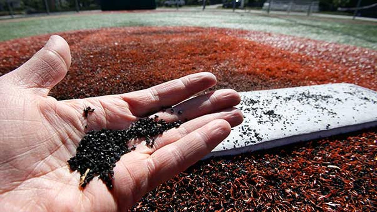 FILE - In this May 17, 2009, file photo tiny a man holds bits of ground-up tires, used as filler between blades of artificial grass, on a playing field made of synthetic turf.