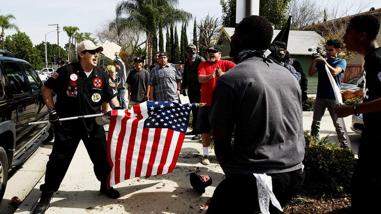A Ku Klux Klansman, left, uses an American flag to fend off angry counter protesters after members of the KKK tried to start a White Lives Matter rally in Anaheim, Calif.