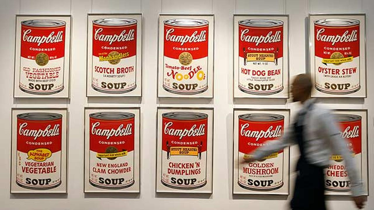 FILE: A Sothebys technician walks past a set of Andy Warhols Campbells Soup screenprints at the auction rooms in London, Friday, March 15, 2013.