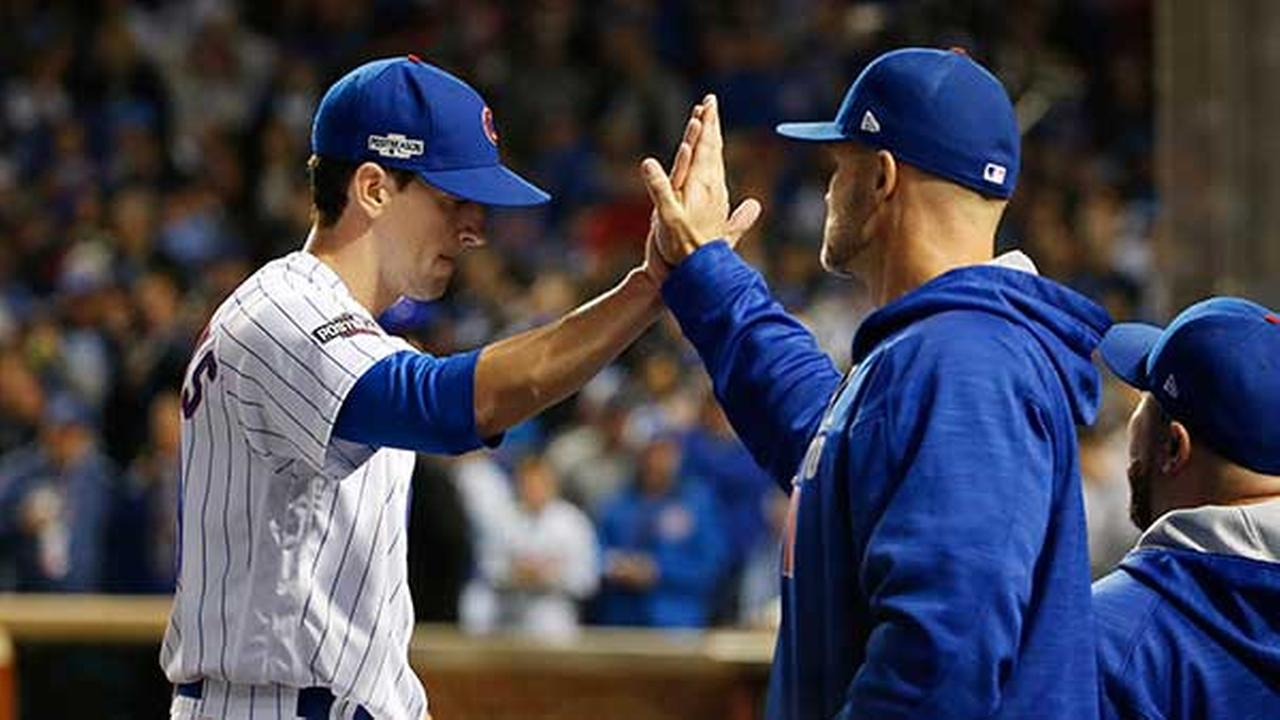 Chicago Cubs starting pitcher Kyle Hendricks, left, is greeted by David Ross after pitching the fifth inning of Game 6 of the National League baseball championship series against t