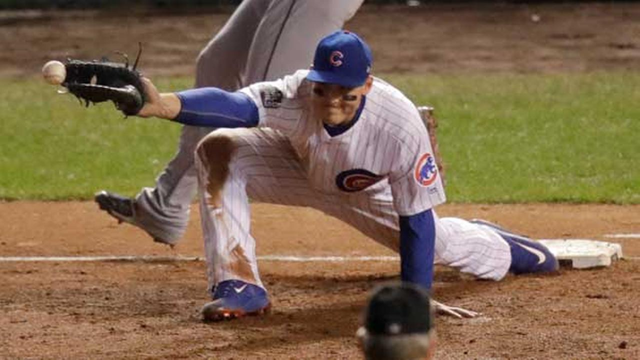 Cleveland Indianss Corey Kluber is safe at first as Chicago Cubs first baseman Anthony Rizzo is unable to catch the throw during the second inning of Game 4.