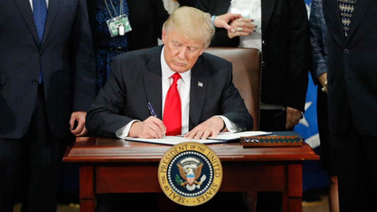 President Donald Trump signs an executive order for border security and immigration enforcement improvements at the Department of Homeland Security in Washington.