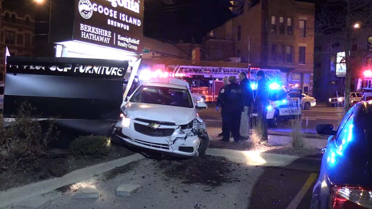 Police investigate a stolen car that crashed into a cab and large lighted sign Thursday night in Lincoln Park.